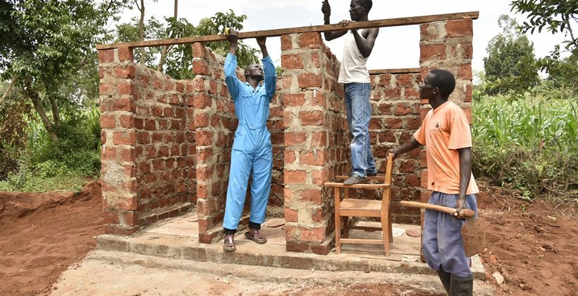 three men building a latrine in Kenya
