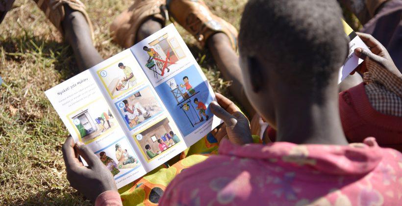 girl reading material about handwashing