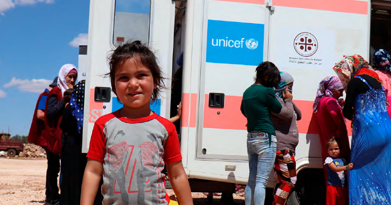 child standing in front of UNICEF mobile health unit